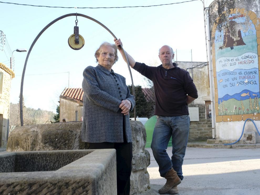 Leonor Corral y el alguacil, Fermín Ortas, cerca del depósito con un mural de la lucha contra la presa.
