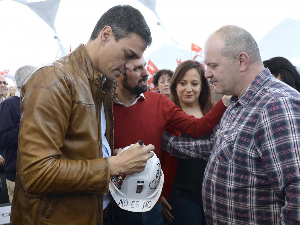 El exsecretario general del PSOE y candidato a las Primarias, Pedro Sánchez, firma un casco como gesto de apoyo al carbón autóctono de un minero leonés, que ha acudido al acto celebrado hoy en Valladolid.