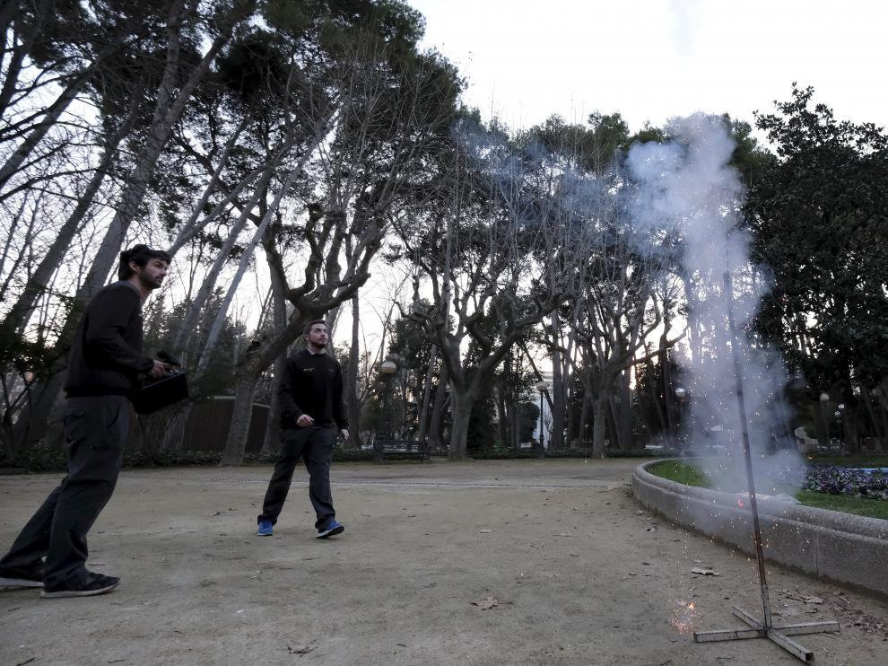 Operarios de Ambién lanzan los cohetes junto a los pinos del parque Miguel Servet.