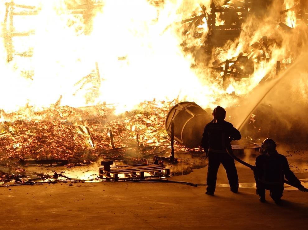 El fuego sigue devorando varios palets apilados junto al almacén. Digital Fraga TV.