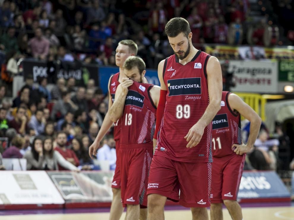 Los jugadores del Tecnyconta Zaragoza se retiran a los vestuarios, cabizbajos, tras encajar una nueva derrota en casa.