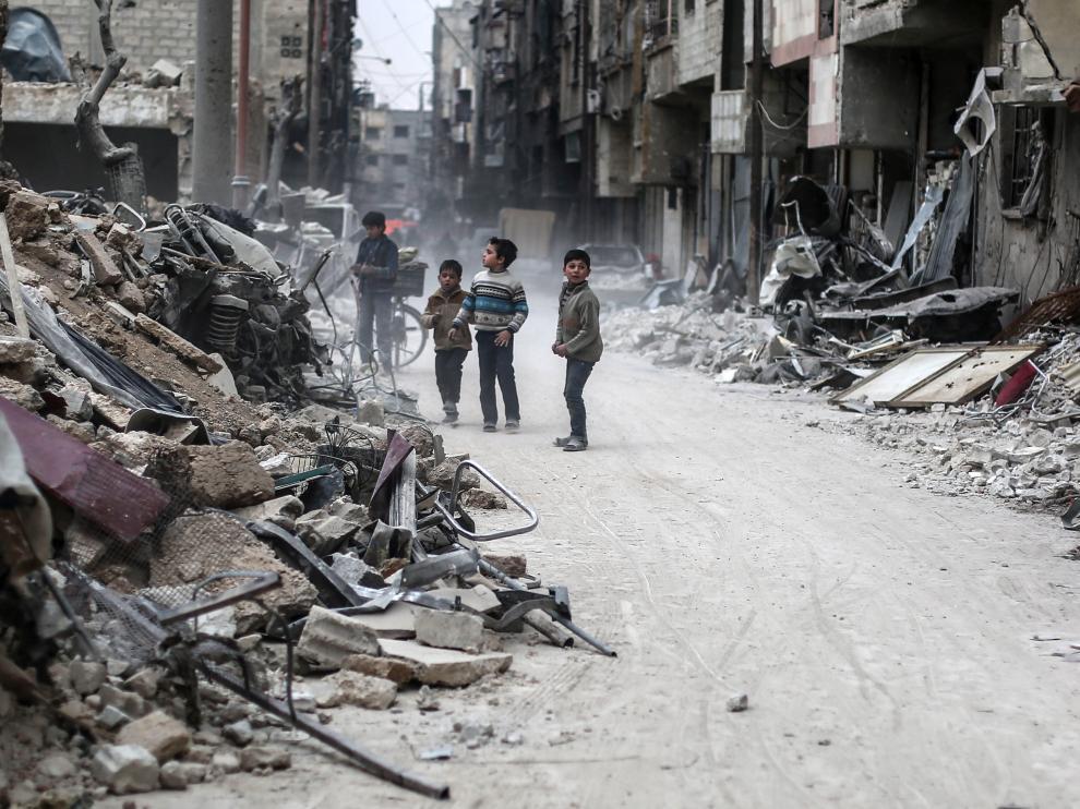 Varios niños sirios buscan entre los escombros de Alepo