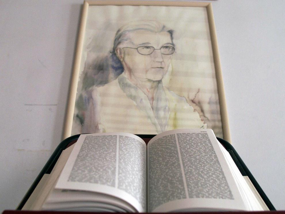 Un ejemplar del diccionario del uso del español, junto a un retrato de María Moliner