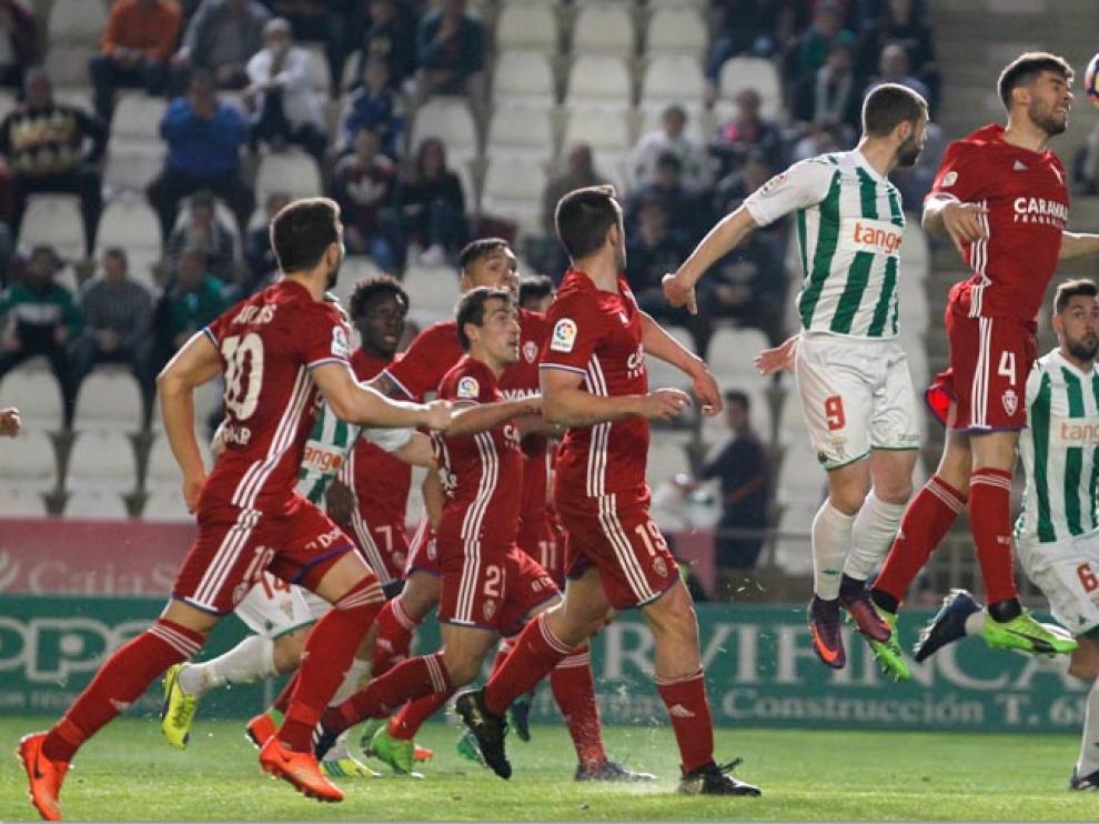 Cabrera intenta despejar de cabeza, ante la mirada de medio equipo zaragocista, un centro sobre el área de Saja en el último Córdoba-Real Zaragoza.