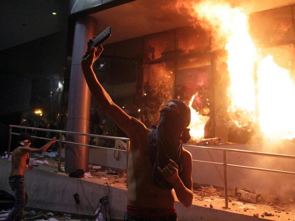 Un manifestante se hace un selfi frente al Congreso en llamas