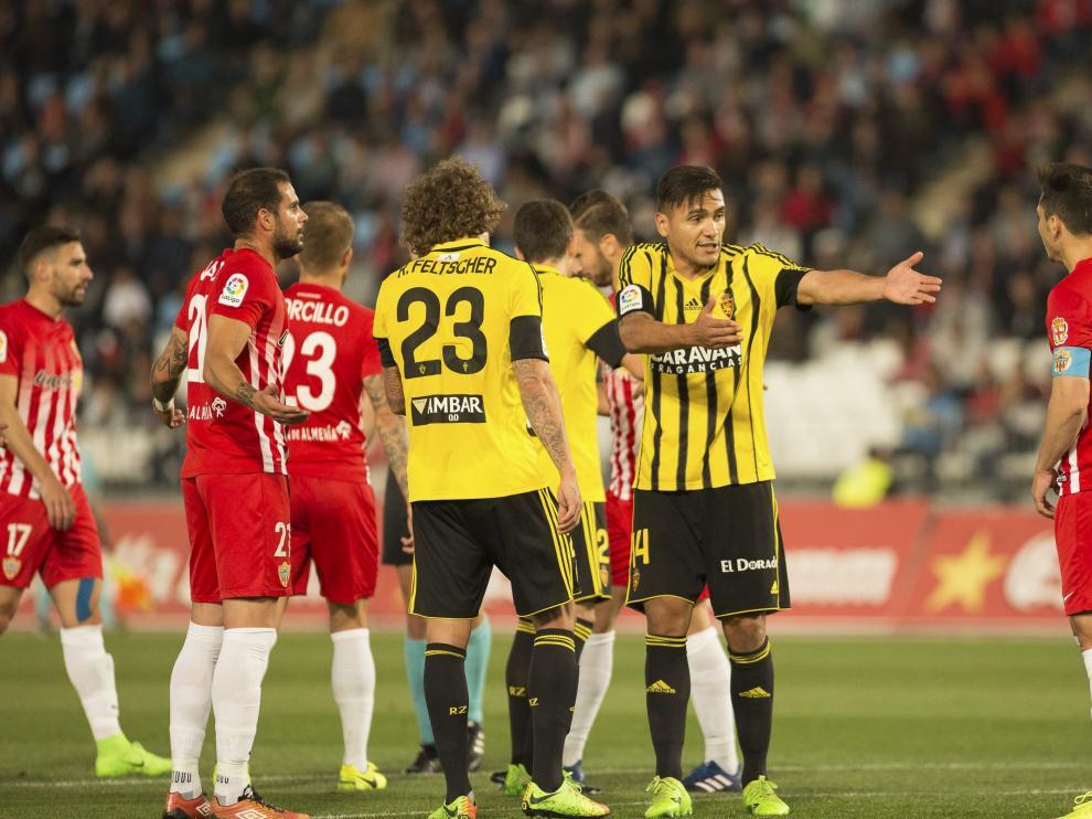 Feltscher, Zapater y Marcelo Silva discuten un lance del partido disputado en Almería.