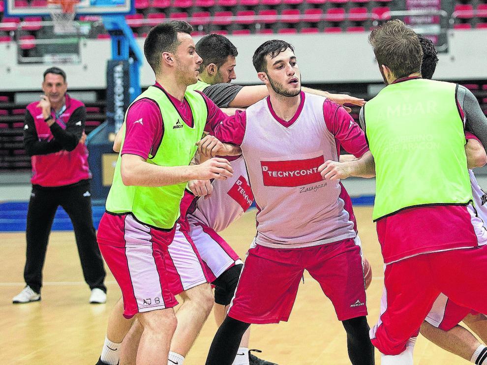 El base Sergi García, en el centro, rodeado de un grupo de compañeros, ante la mirada del técnico Luis Guil, al fondo.