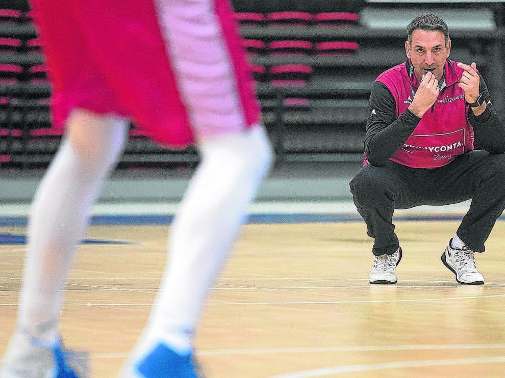 El entrenador Luis Guil, agachado y con el silbato en la boca, observa los movimientos de sus jugadores durante un entrenamiento.