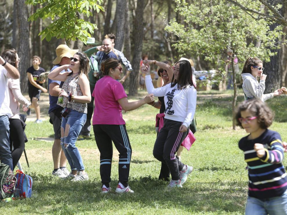 Un grupo de familias con hijos de distintas edades bailan al son de la charanga antes de empezar a tomar el vermú en el cerro.