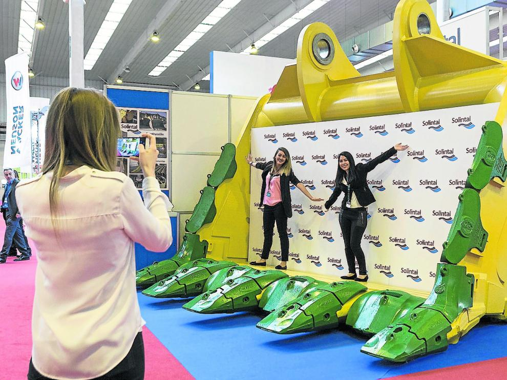 Dos jóvenes se hacen una foto dentro de una gigantesca pala que se muestra desde ayer en Smopyc, en la Feria de Zaragoza.