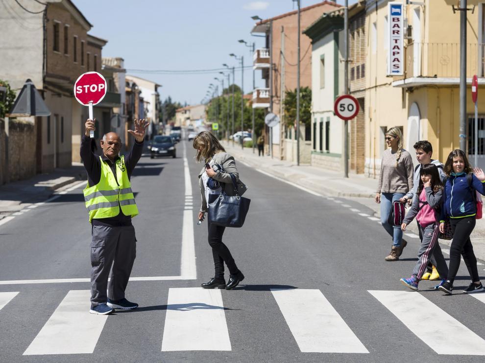José María Gracia 'Machillo' controla el tráfico mientras varios vecinos cruzan la N-232.