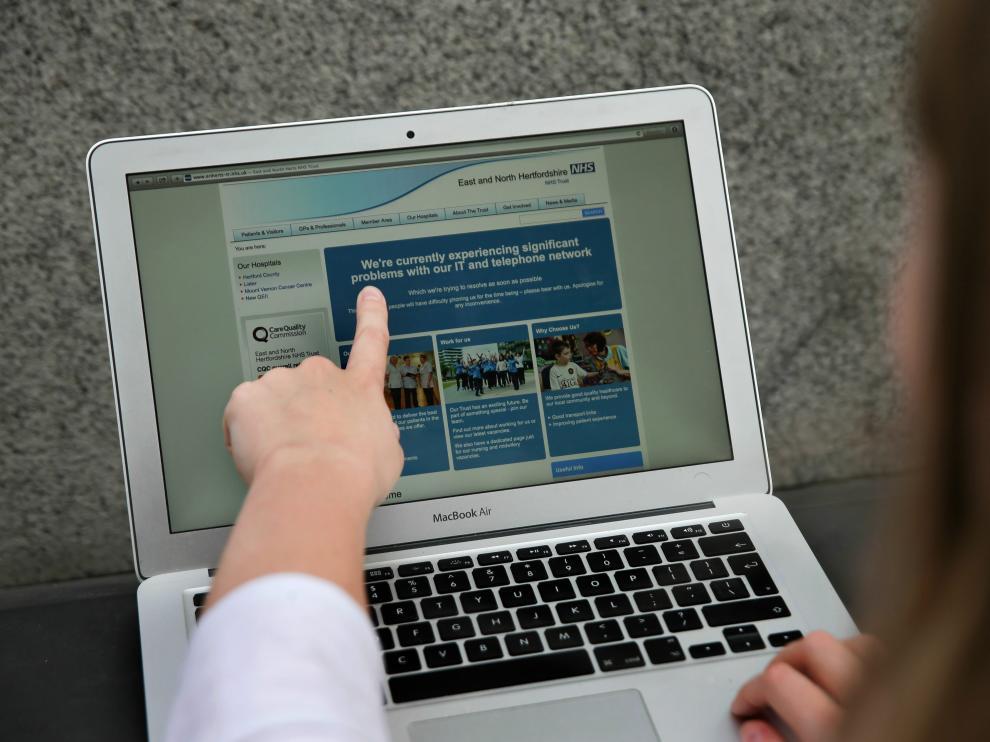 Un empleado del sistema británico de salud señala un mensaje que alerta de los problemas en la red.