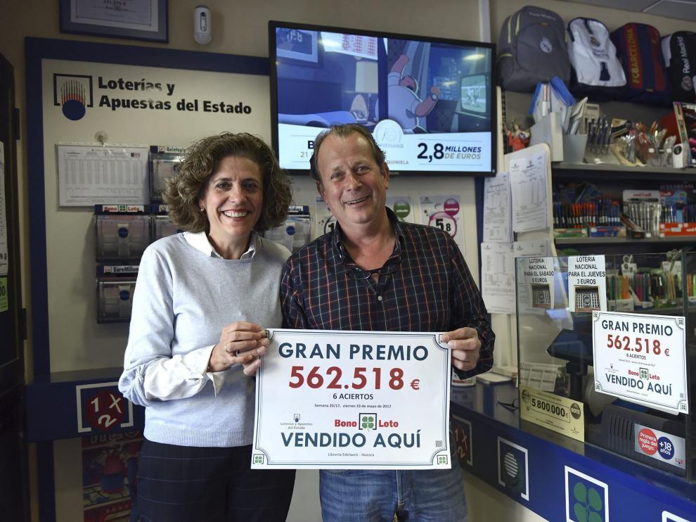 Pilar Lafarga y Luis Beired posan felices con el cartel que certifica el premio de la Bonoloto.