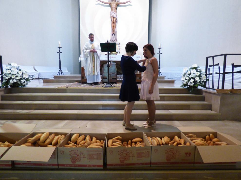 La presidenta del Gremio de Panaderos, Ana Marcén, impone la medalla a la mayordoma de este año, Laura Lumbreras.