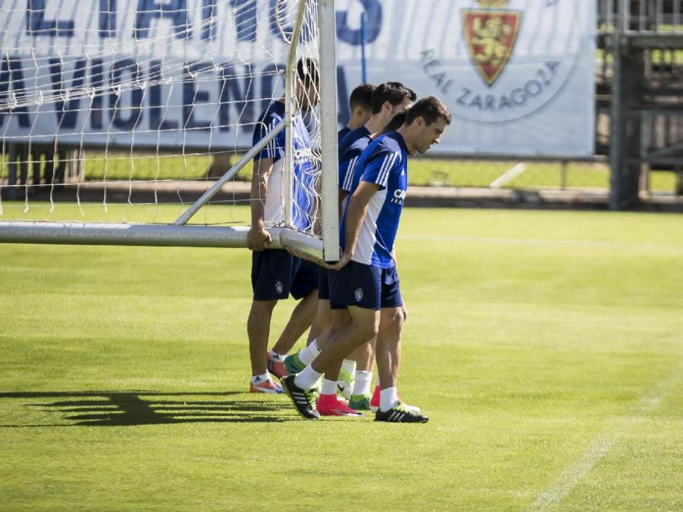 Varios jugadores del Real Zaragoza trasladan una portería móvil al inicio del entrenamiento.