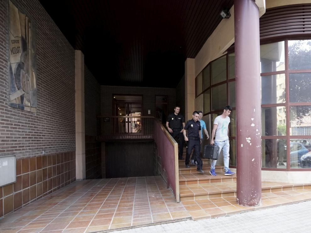 Varios policías abandonan el edificio en el que se produjeron los hechos tras inspeccionar el escenario.