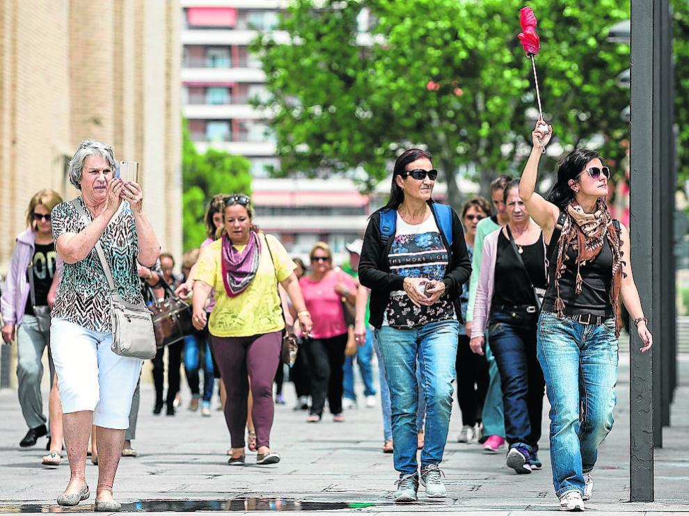 Un grupo de turistas siguen a su guía en el entorno de la plaza del Pilar.