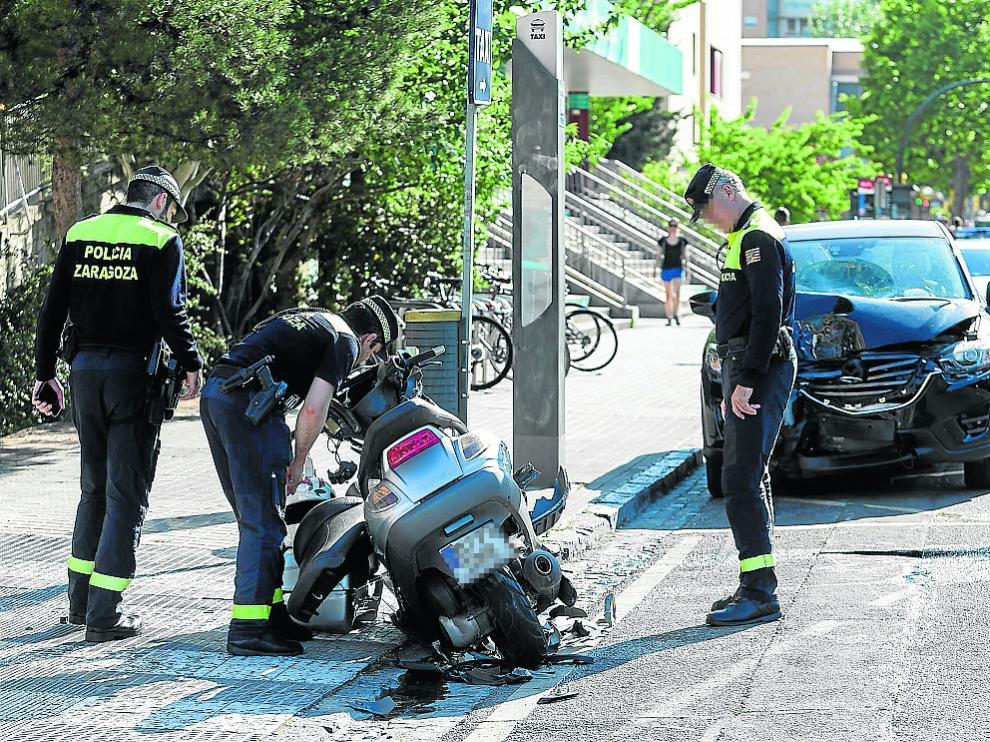 Tres agentes de la Policía Local inspeccionan la motocicleta del accidentado.