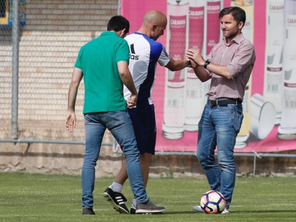 Lalo Arantegui, director deportivo del Real Zaragoza, saluda a un serio Láinez al inicio del entrenamiento de este lunes, en presencia de José Mari Barba, el secretario técnico.