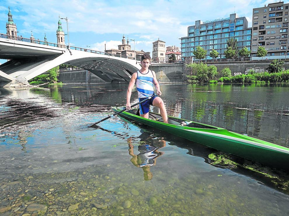 Bruno Herrero posa con los colores del CNHelios, sobre su embarcación, en el río Ebro de Zaragoza.