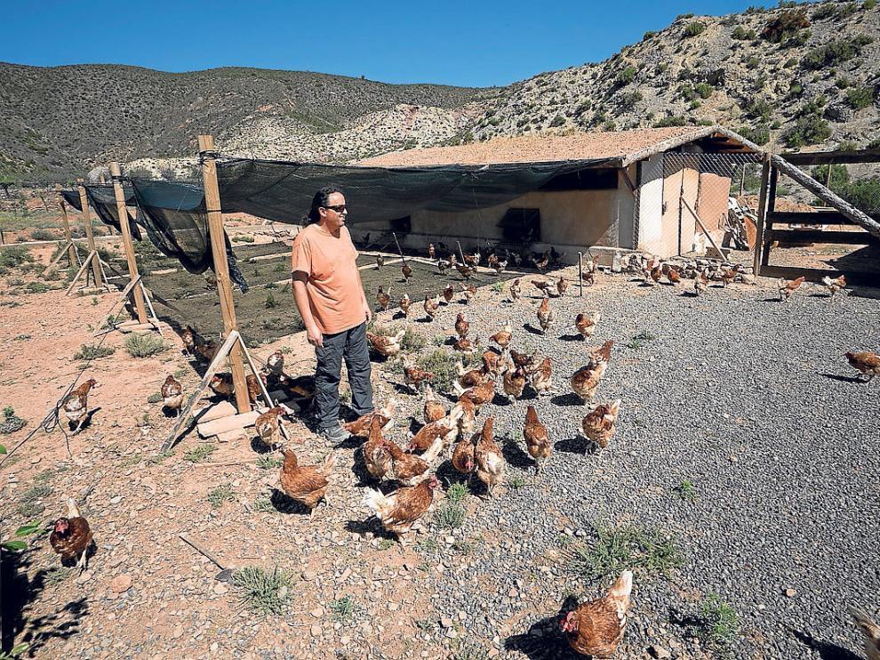 El avicultor Miguel Ángel Armengod delante de una de las casetas hechas con barro.
