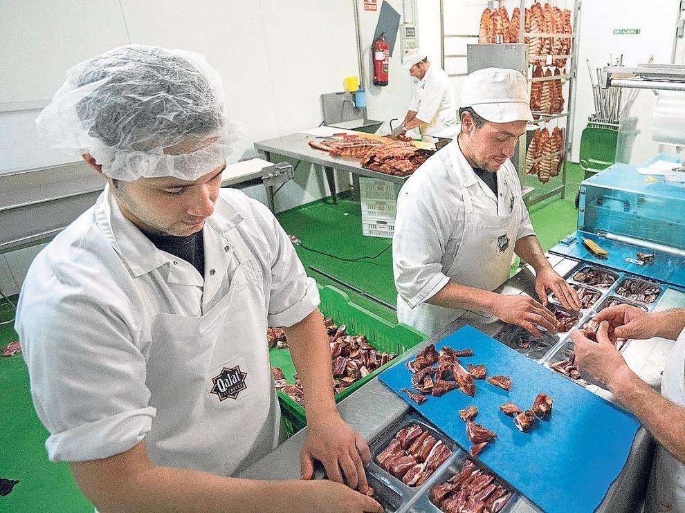 Un grupo de trabajadores de Cárnicas Santa Elena envasan productos de Denominación de Origen bajo la marca Qalat.