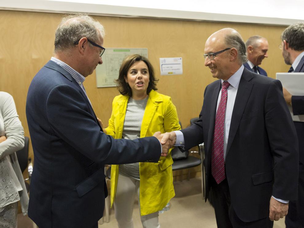 El consejero Gimeno saluda al ministro Montoro ante la vicepresidenta Saenz de Santamaría, este jueves.