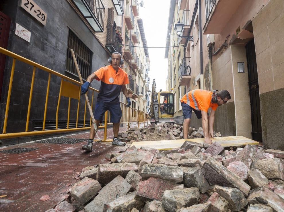 Dos operarios trabajan en la retirada del adoquinado de la calle de San Agustín.