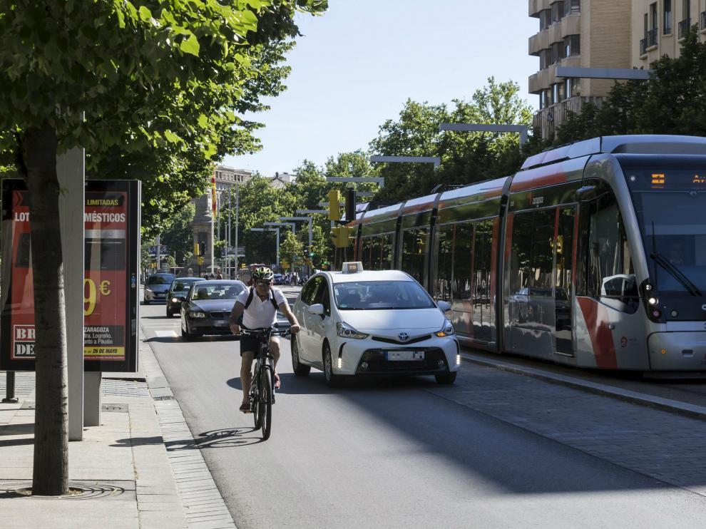 Un taxi rebasa a un ciclista utilizando la zona empedrada del Paseo de la Independencia