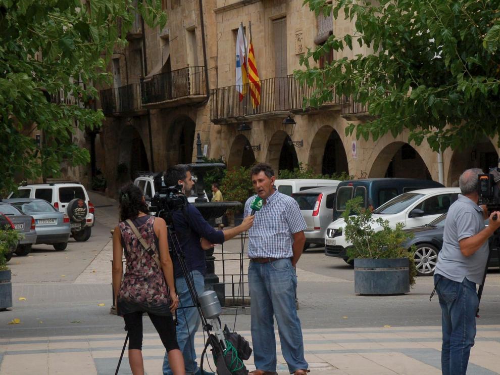 El alcalde Joaquim Paladella, en el centro de la foto, atiende a una televisión en la plaza de Batea, delante del Ayuntamiento.