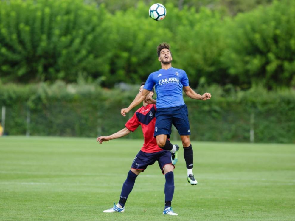 Javi Ros se lleva un balón por alto ante el jugador del Boltaña.