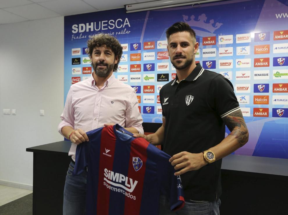 Luso Delgado posa con la camiseta del Huesca junto a Emilio Vega.