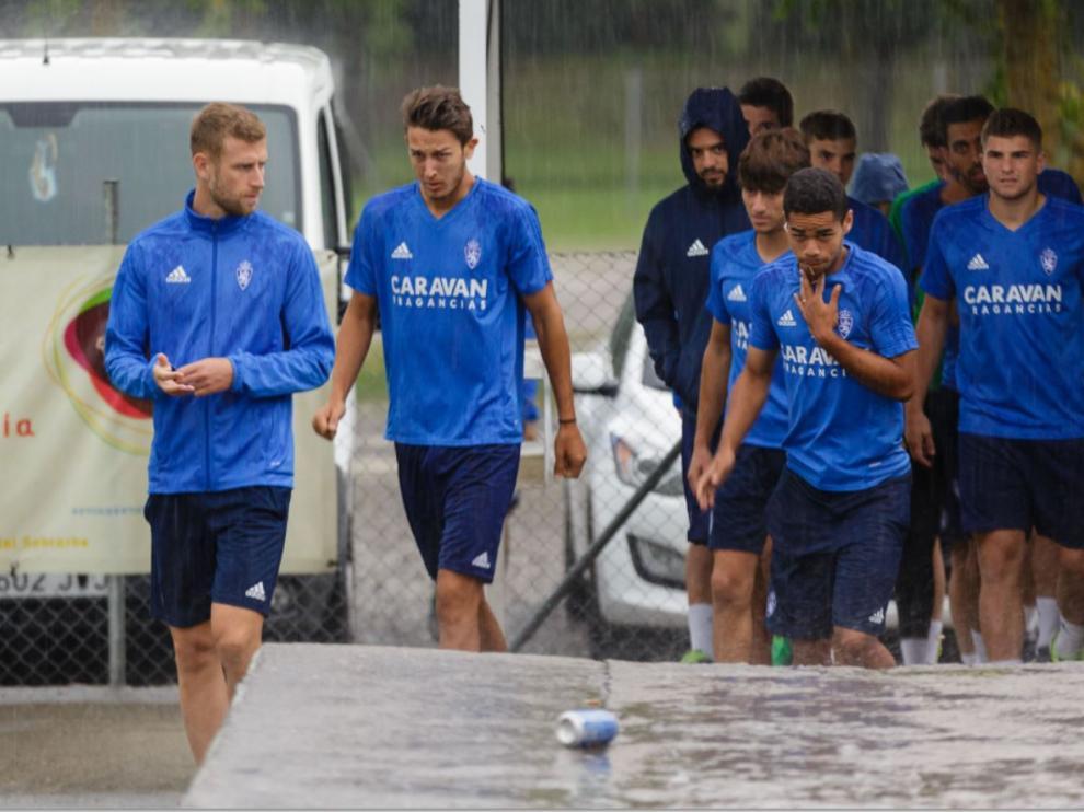 Los jugadores del Real Zaragoza llegan al campo de Villaboya de Boltaña en medio de un intenso aguacero de tormenta en la mañana de este viernes.