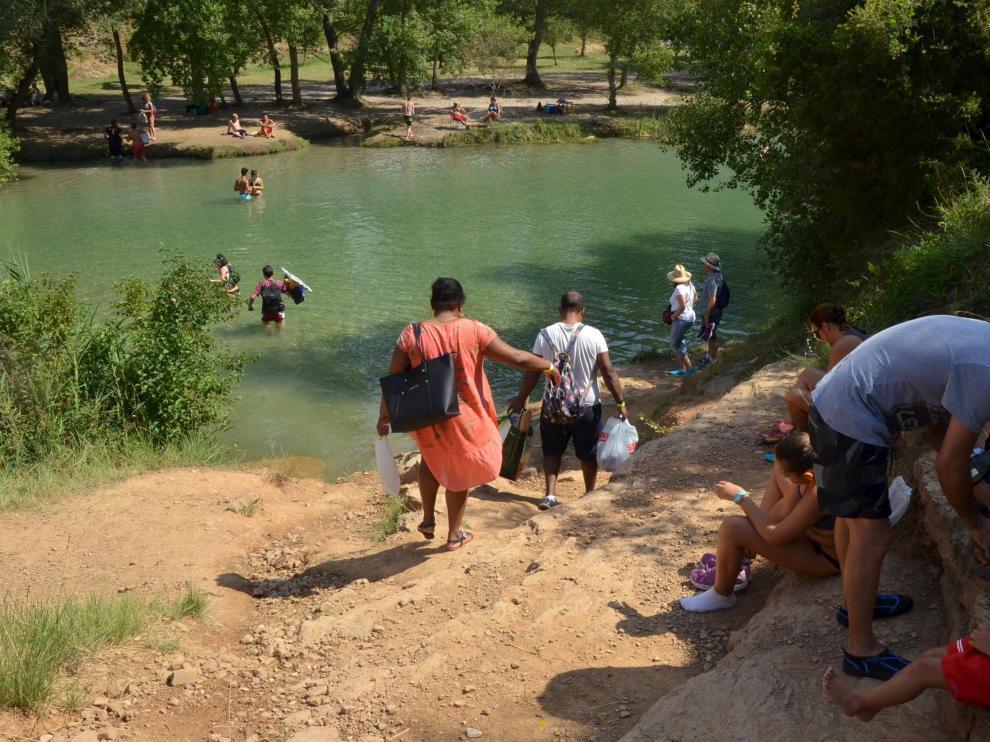 Algunos bañistas que acuden al salto de Bierge cruzan el río para encontrar el mejor sitio.