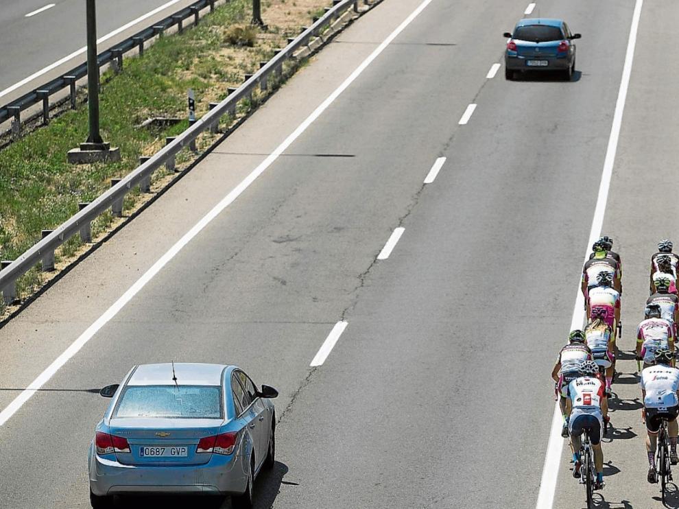 Un grupo de ciclistas circula por la carretera de Valencia mientras un vehículo adelanta correctamente.