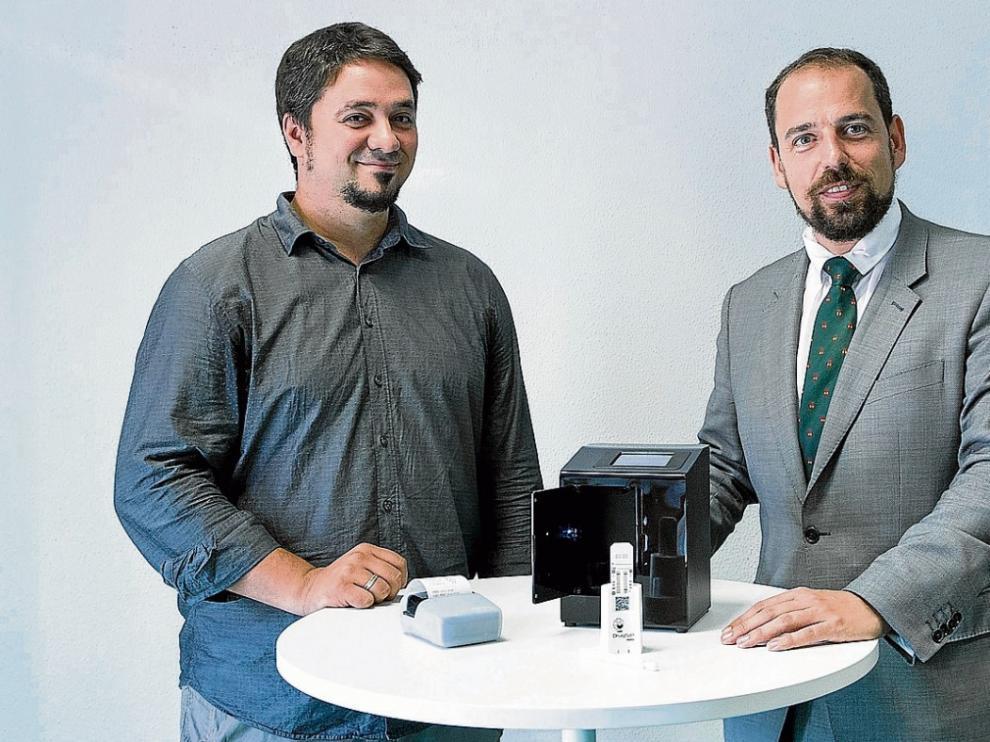 Miguel Ángel Roncalés (derecha), junto a Carlos Sánchez, ingeniero de I+D de la compañía aragonesa, con el nuevo Drugsip Mobility.