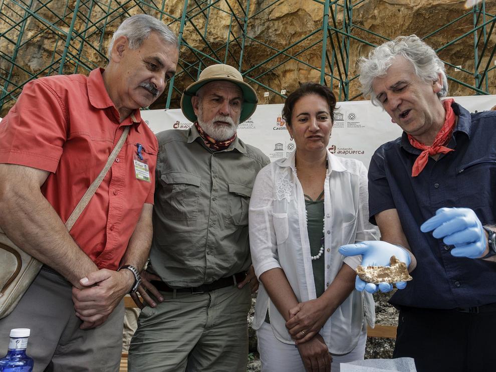 Los codirectores de Atapuerca, José María Bermúdez de Castro, Eudald Carbonell y Juan Luis Arsuaga, junto a la consejera de Cultura y Turismo de Castilla y León, María Josefa García, muestran los restos de neandertales hallados en el yacimiento.