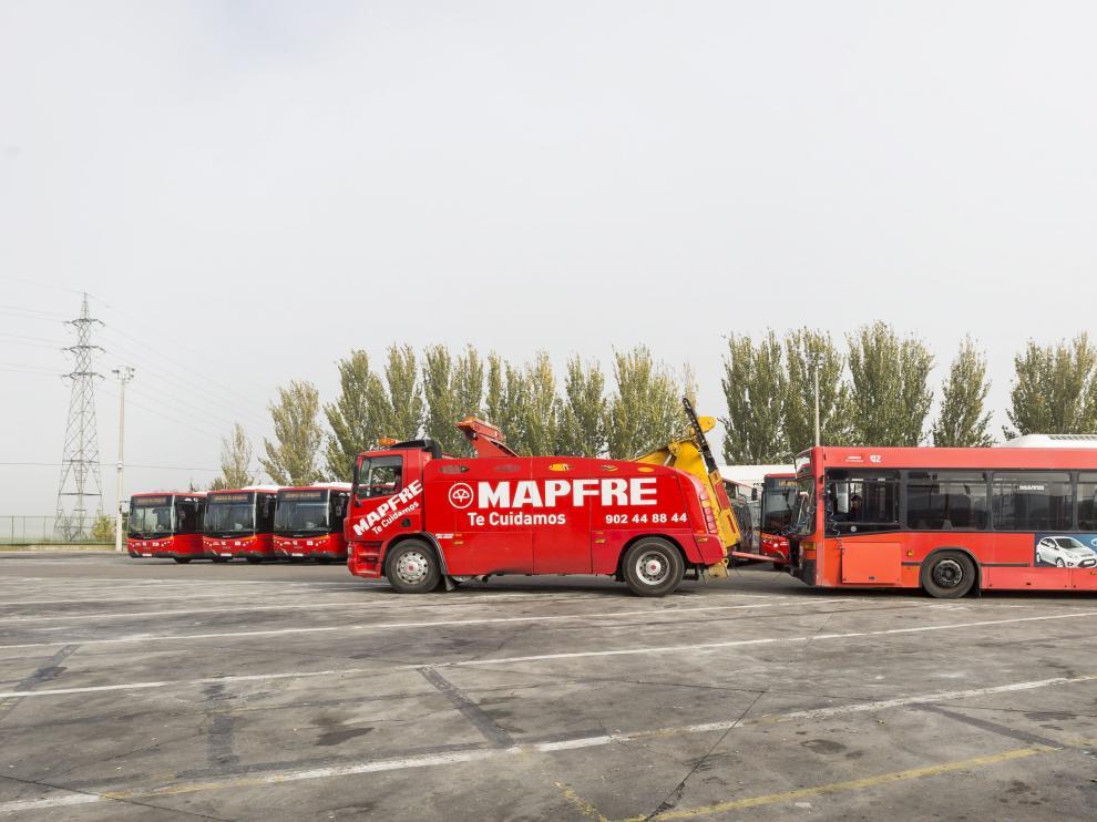 Una grúa con un autobús averiado pasa por delante de los once nuevos vehículos que se incorporaron a la flota el pasado mes de noviembre.