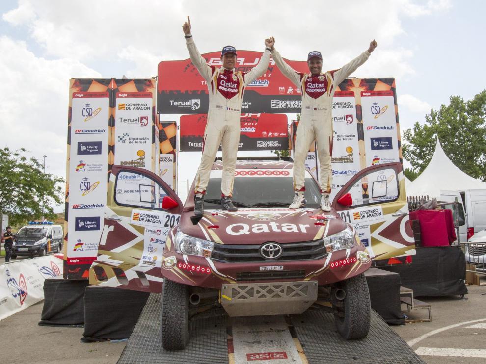 Nasser Al Attiyah celebra su triunfo en la prueba aragonesa junto a su copiloto, Mathieu Baumel, encima de su coche, un Toyota Hilux.