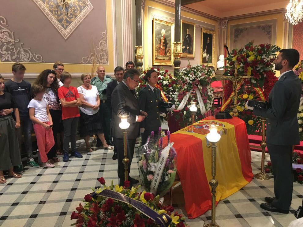 El ministro, en la visita a la capilla ardiente, imponiéndole la condecoración en presencia de la familia del guardia civil fallecido.