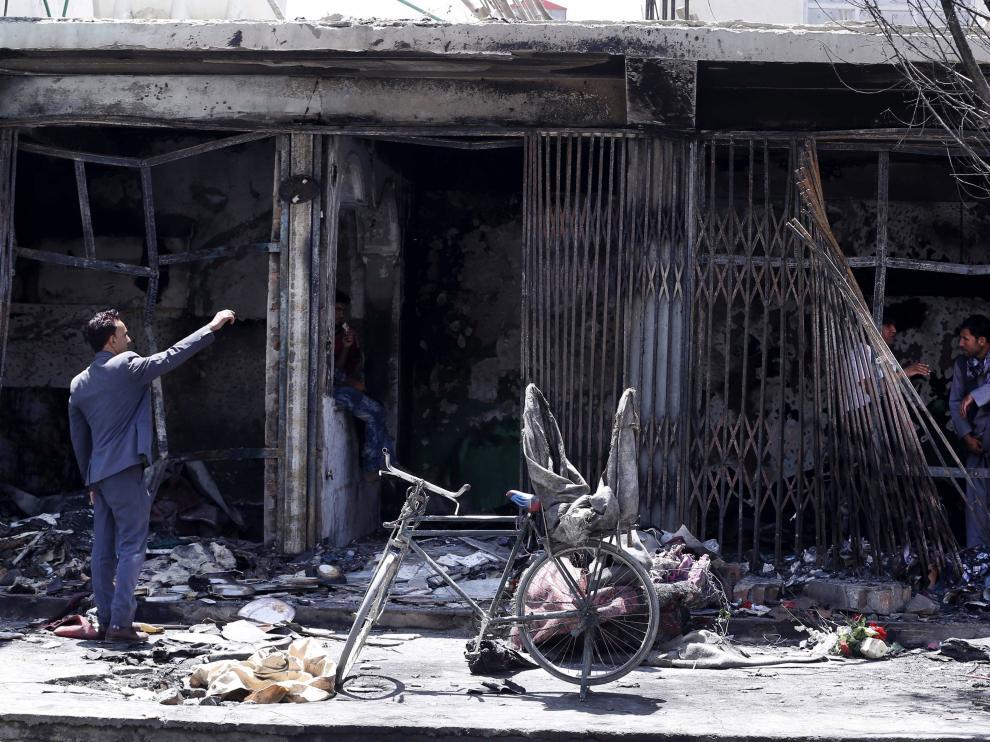 Afganos comprueban los daños en un establecimiento destrozado como consecuencia del atentado terrorista perpetrado este martes en Kabul.