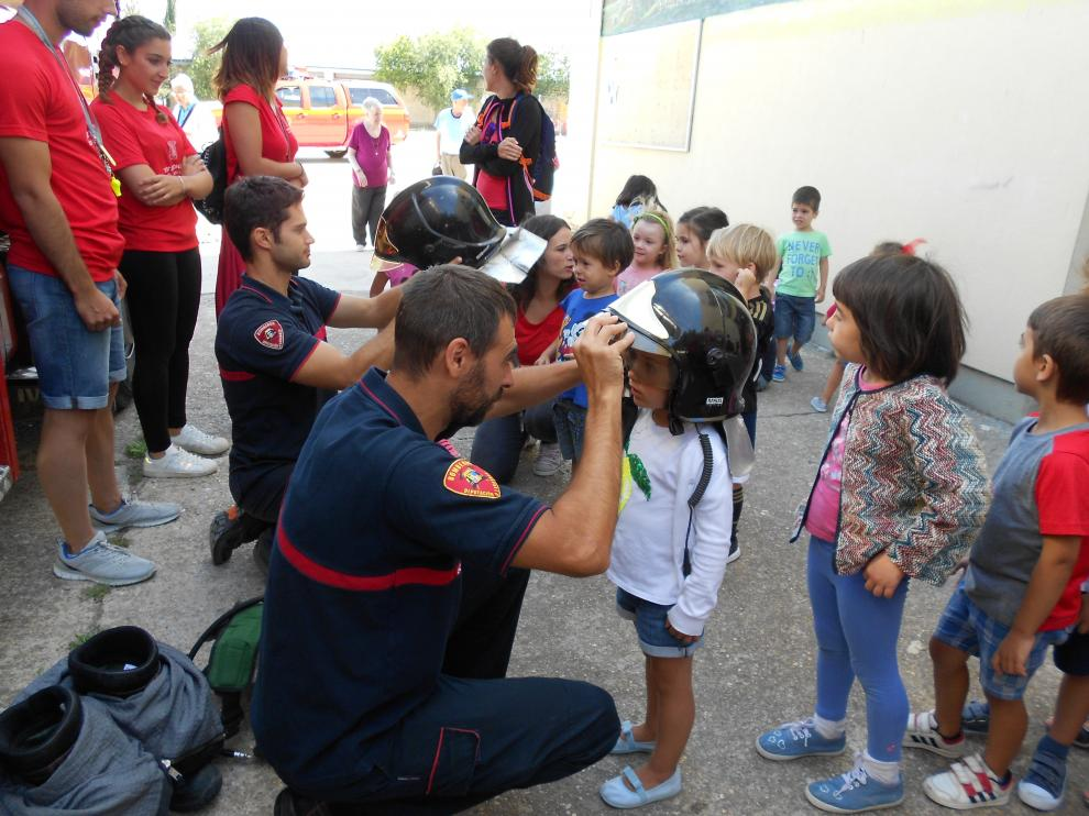 Los niños han podido probarse los cascos de los bomberos.