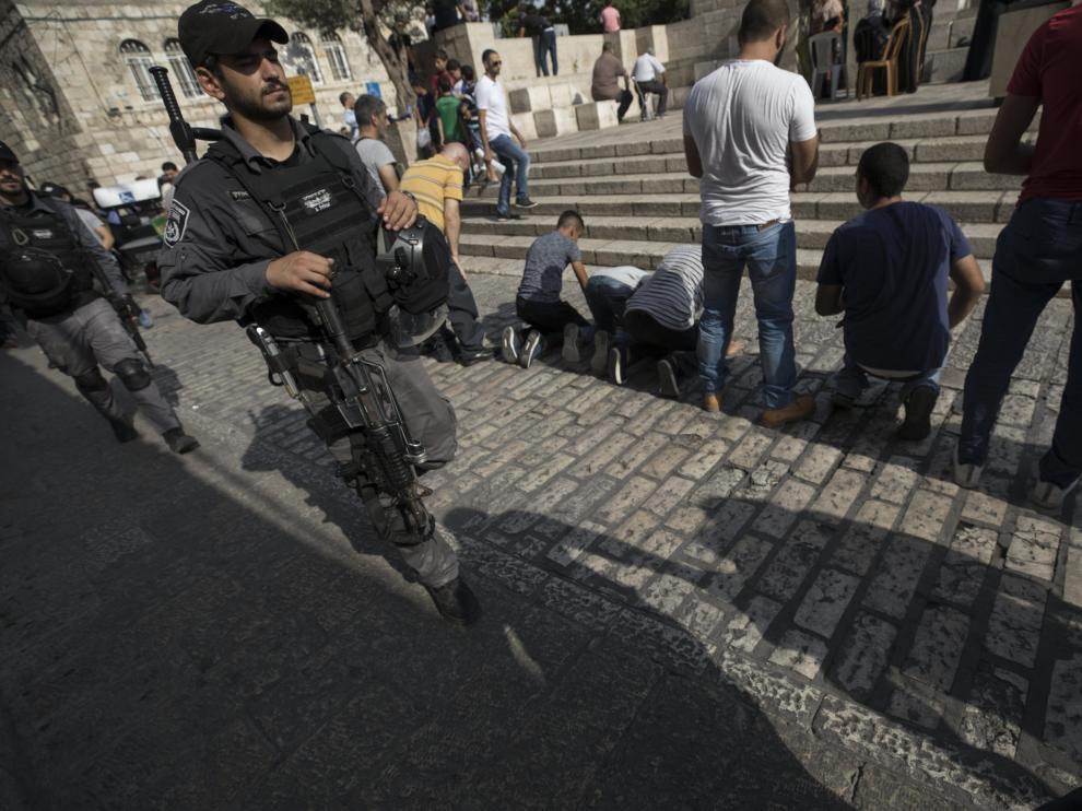 Un militar israelí patrulla mientras varios palestinos rezan fuera de la Puerta de los Leones, el acceso principal al complejo en el que se encuentra la Mezquita de Al Aqsa en Jerusalén (Israel) hoy, 24 de julio del 2017. Siguen los enfrentamientos diarios entre palestinos y fuerzas de seguridad israelíes por la instalación de nuevas medidas de seguridad en torno a la Explanada de las Mezquitas, tras el ataque mortal el pasado día 14 en el que murieron dos policías y sus tres atacantes.