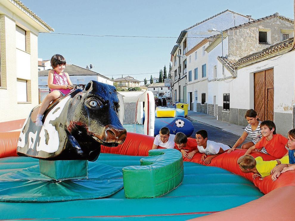 Varios niños disfrutan de los hinchables y el toro mecánico instalados en una de las calles del municipio oscense.