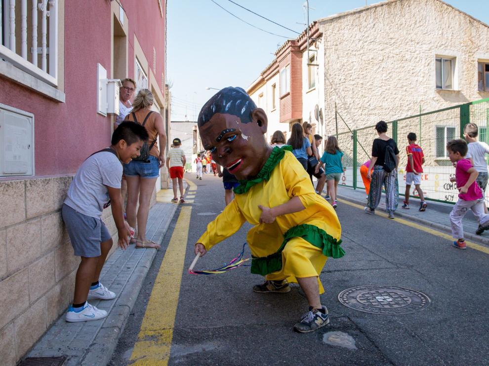Un cabezudo acorrala a un niño que se ríe al esquivar el azote.