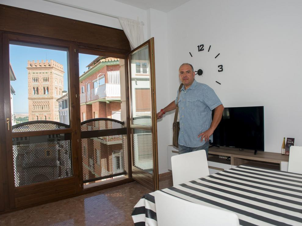 Rafael Sanz en su piso de Teruel, desde el que se ve la torre mudéjar del Salvador.