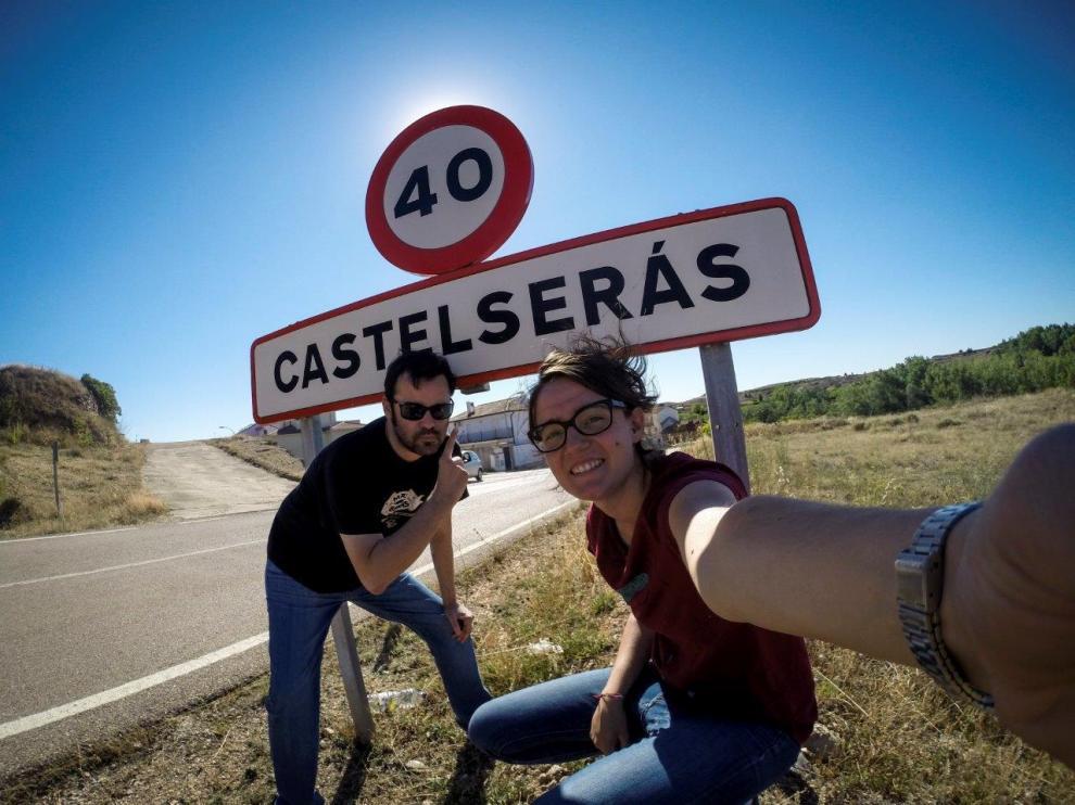 Laura Uranga y Pablo Ferrer junto al cartel de entrada a Castelserás