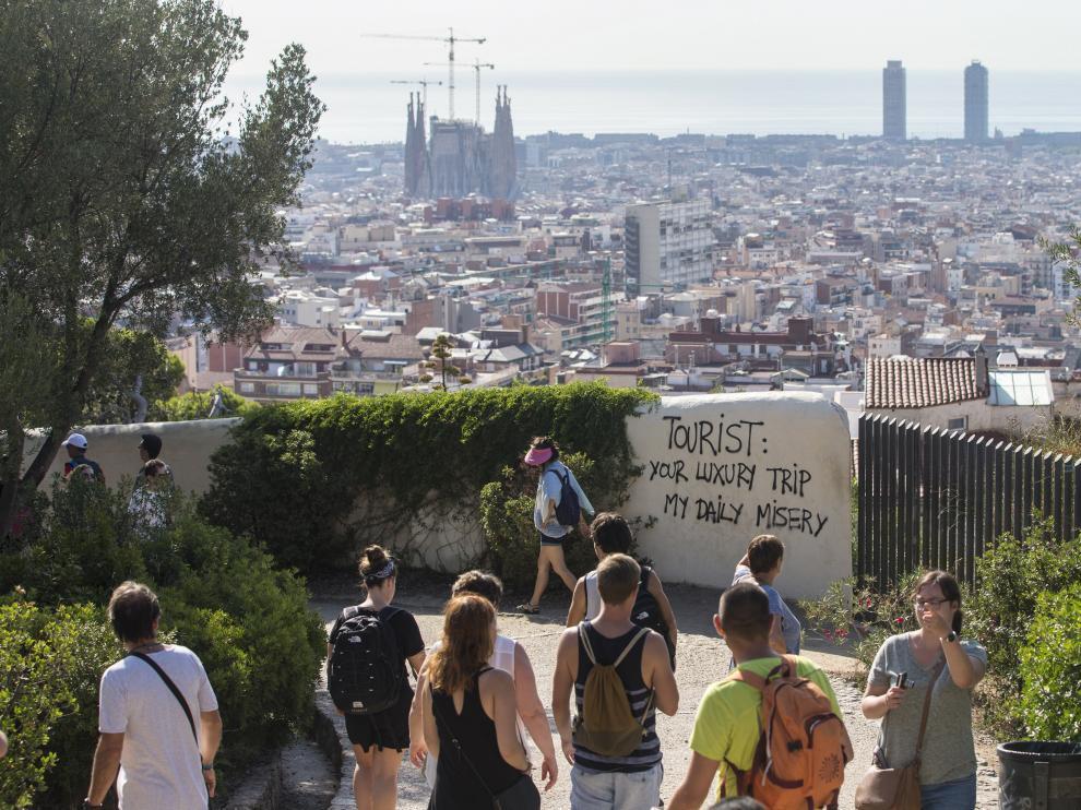 Un grupo de turistas pasea por los alrededores del Parque Guell de Barcelona, donde últimamente ha  aparecido pintadas contrarias al turismo masificado.