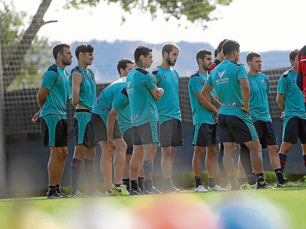 Los futbolistas del Huesca escuchan las explicaciones de los técnicos nada más arrancar la sesión de ayer en el Montearagón.