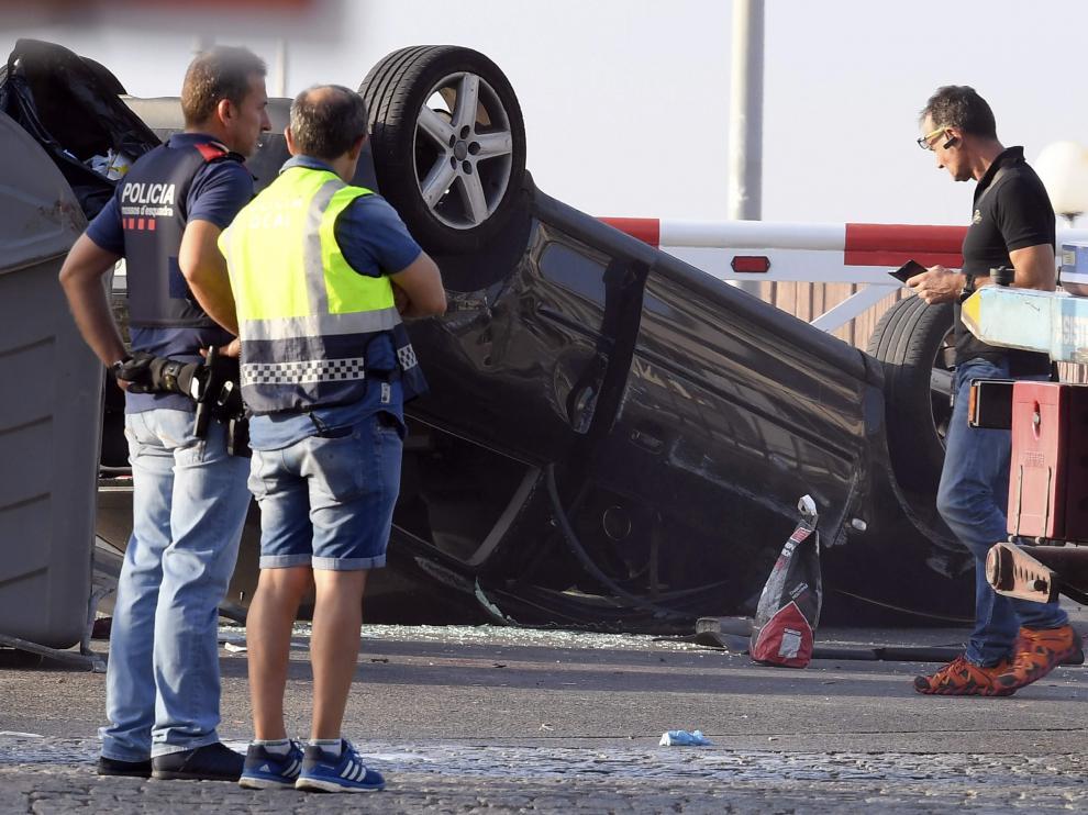Agentes de los Mossos d'Esquadra examinan el vehículo Audi A3 donde iban los cinco terroristas, en el paseo marítimo de Cambrils.